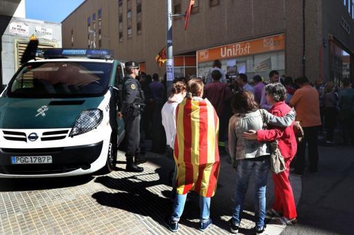 Numerosas personas permanecen ante la oficina de la empresa de mensajería Unipost en Terrassa (Barcelona), durante el registro que agentes de la Guardia Civil han efectuado en dicho local.