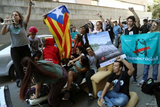 Numerosas personas protestan ante la oficina de la empresa de mensajería Unipost en Terrassa (Barcelona), donde agentes de la Guardia Civil han realizando un registro en el que se han incautado de abundante documentación relacionada con el censo del referéndum del 1-O.