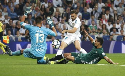 El delantero del Real Madrid, Borja Mayoral, golpea el balón ante los jugadores del Real Betis, el guardameta Adán y el defensa argelino AissaMandi.
