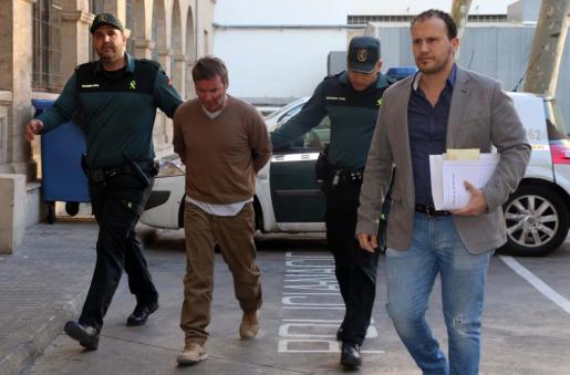 El acusado, entre dos agentes de la Guardia Civil, cuando fue presentado en los juzgados.