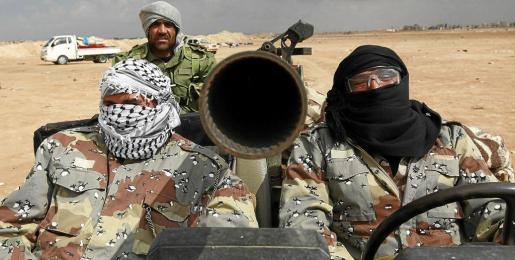 Rebeldes libios regresan con su vehículo después de atacar posiciones cercanas a la localidad de Ajdabiya.