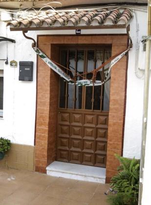Entrada de la vivienda de Huelva donde se encontraron los cuerpos sin vida de un hombre y una mujer, que convivían con cuatro niños.