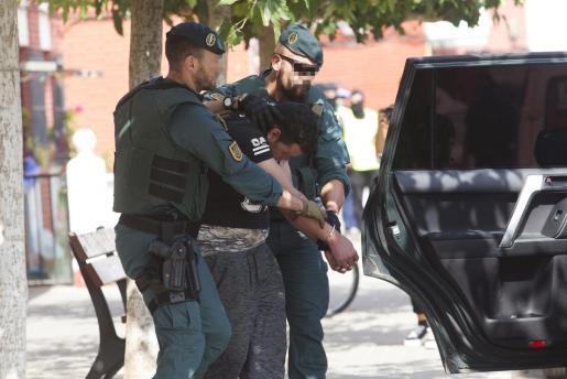 Agentes de la Guardia Civil conducen al joven marroquí detenido por su supuesta relación con la célula yihadista que cometió los atentados de agosto en Cataluña.