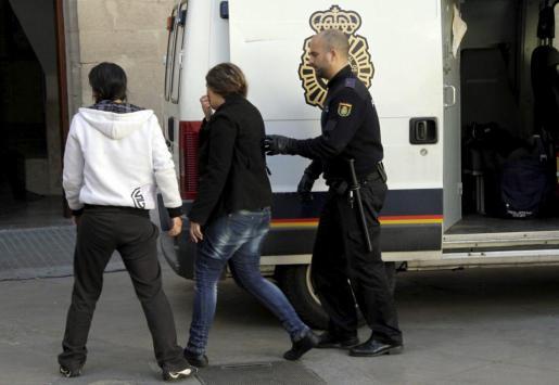 Un agente de policía acompaña a dos de las detenidas al juzgado de guardia de Vía Alemania.