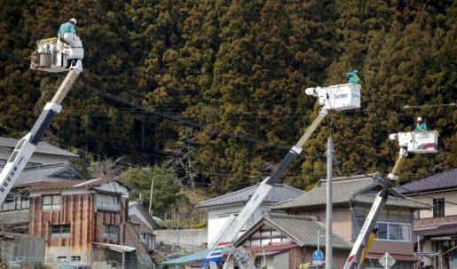 Empleados de una compañía energética trabajan en un cable eléctrico en Rikuzentakata.