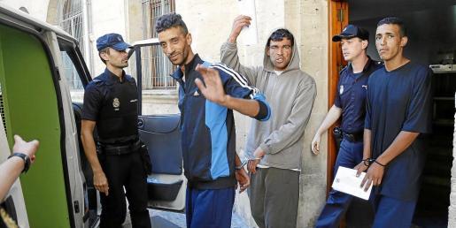Tres de los inmigrantes puestos este miércoles a disposición judicial se disponen a subir al furgón policial.