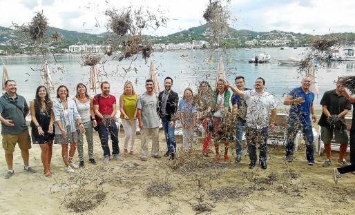 Representantes de entidades medioambientales y de las siete administraciones pitiusas lanzan posidonia al aire en Talamanca.