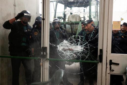 Agentes, rompiendo el cristal del colegio de Sant Juli de Ramis.