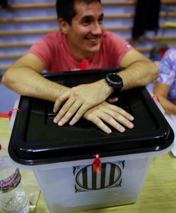 Un integrante de una mesa electoral sujeta una urna.
