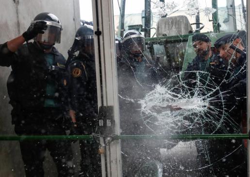 Imagen de los guardias civiles usando la fuerza para entrar en uno de los colegios electorales del 1-O.