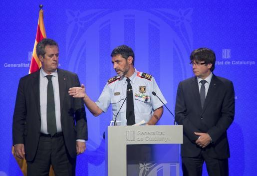 El presidente catalán, Carles Puigdemont (d), junto al conseller de Interior, Joaquim Forn (i), y el mayor de los Mossos d'Esquadra, Josep Lluís Trapero (c).