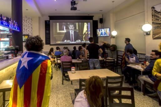 Varias personas escuchan con atención el discurso del Rey Felipe VI sobre la situación en Cataluña, un pronunciamiento que fue muy comentado en las principales redes sociales.