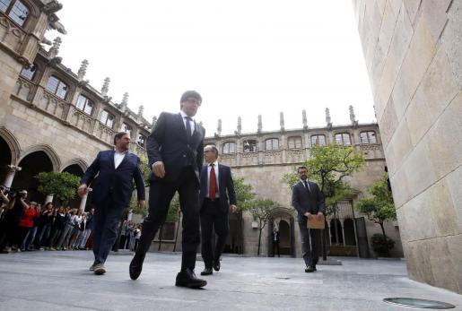 El presidente de la Generalitat, Carles Puigdemont, junto al vicepresidente Oriol Junqueras (i), y el conseller de Presidencia, Jordi Turull (d), a su llegada al Parlament de Cataluña.