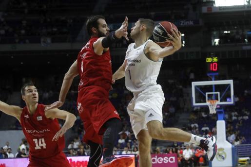 El escolta francés del Real Madrid Fabien Causeur (d) intenta avanzar con el balón ante la oposición del ala-pívot serbio del Tecnyconta Zaragoza Nikola Dragovic (c).