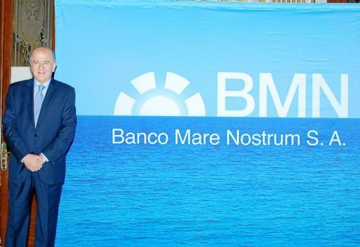 Carlos Egea, presidente de Cajamurcia y Caja Mare Nostrum, frente al logotipo de BMN.