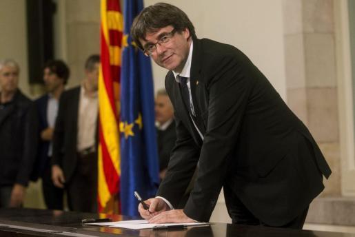 El presidente de la Generalitat, Carles Puigdemont, firma el documento después de comparecer ante el pleno del Parlament para trasladar los resultados de la jornada del 1-O.