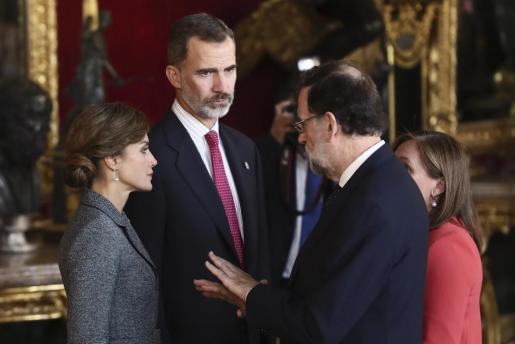 Los Reyes conversan con el presidente del Gobierno, Mariano Rajoy, acompañado de su mujer Elvira Fernández a su llegada a la tradicional recepción con motivo del Día de la Fiesta Nacional.