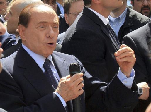 El primer ministro italiano, Silvio Berlusconi, utiliza un micófono para conversar con sus seguidores frente al Tribunal Penal de Milán (Italia).