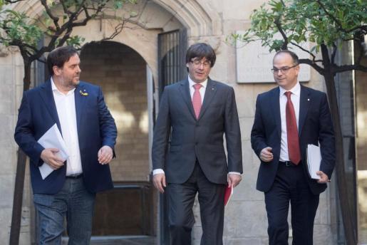 El presidente de la Generalitat, Carles Puigdemont, el vicepresidente, Oriol Junqueras (i), y el conseller de Presidencia, Jordi Turull (d), a su llegada a la reunión semanal del gobierno catalán.