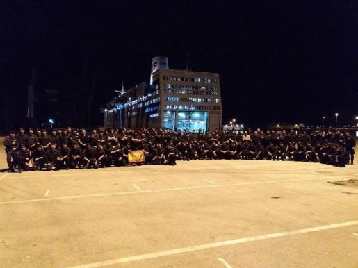 Policías alojados en un barco del puerto de Barcelona posan frente al buque. A pesar de la imagen, diversas voces han alzado la voz criticando sus condiciones, casi un mes después de llegar a su destino provisional.