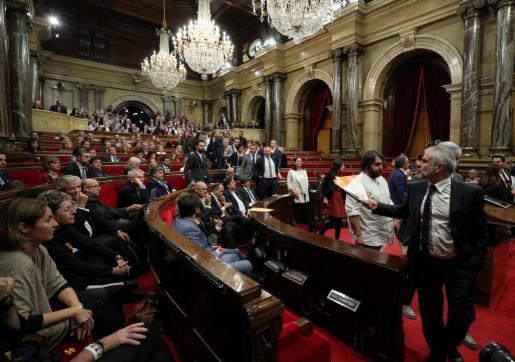 Diputados de diferentes partidos abandonan el Parlament de Cataluña durante las votaciones.