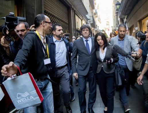 El presidente cesado de la Generalitat de Cataluña, Carles Puigdemont (c), acompañado por su esposa, Marcela Topor, en su paseo por Girona el sábado pasado.