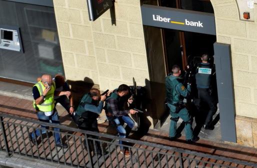 Imagen de los agentes, entrando a la sucursal bancaria.