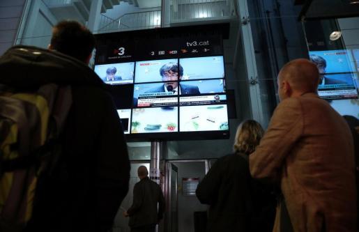 Ciudadanos siguen en el mercado de La Boqueria de Barcelona la comparecencia de Puigdemont desde Bruselas.