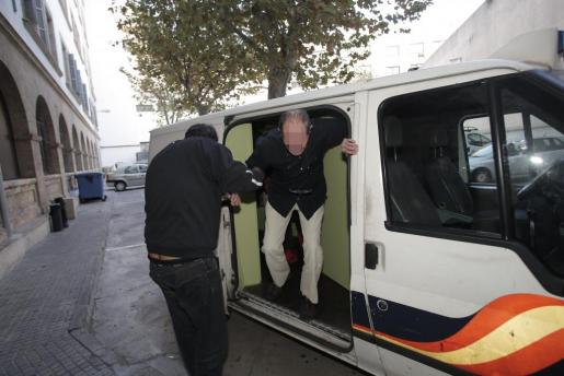 El sospechoso baja del furgón policial en el juzgado de guardia.