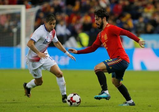 El jugador malagueño del Real Madrid y la selección española, Isco, conduce el balón ante la presión del jugador de Costa Rica Gamboa.
