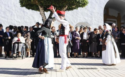 Dos jóvenes de la Colla de Santa Gertrudis hacen una demostración de ball pagès ante la atenta mirada de parte de los mayores homenajeados.