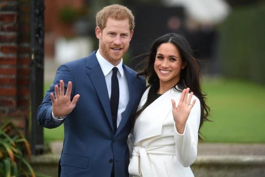 El príncipe Enrique de Inglaterra camina junto a su prometida, la actriz estadounidense Meghan Markle, tras anunciar su compromiso en el Jardín Sunken del Palacio Kensington, en Londres.