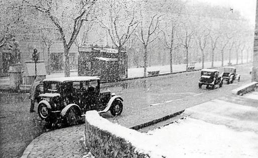 La Rambla, bajo un manto de nieve en 1936, con algunos coches circulando bajo los copos.