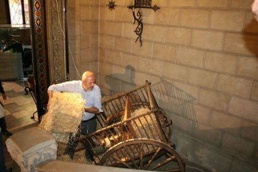 Ensenyat, en plena tarea, carga un carro pagès postrado detrás del Nacimiento.