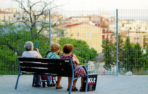 Tres mujeres pensionistas descansan sentadas en un banco después de realizar unas compras.