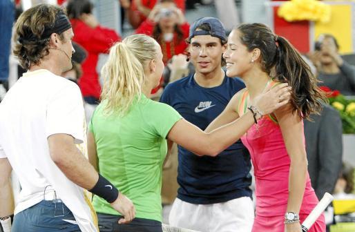 Los tenistas Carolina Wozniacki (2i) y Carlos Moyá saludan a la pareja formada por Anna Ivanovic (d) y Rafael Nadal al finalizar el partido de dobles de exhibición que han disputado durante el acto 'Por un revés al sol' que la Fundación de Félix Mantilla contra el cáncer de piel celebrado en la Caja Mágica de Madrid.