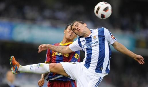 El jugador del F.C. Barcelona, Thiago Alcántara lucha por un balón con el jugador de la Real Sociedad Antonie Griezmann.
