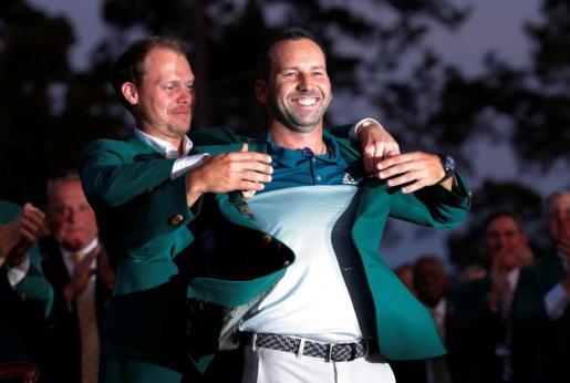 El española Sergio Garcia recibe la tradicional chaqueta verde tras ganar el Masters de Augusta de golf.