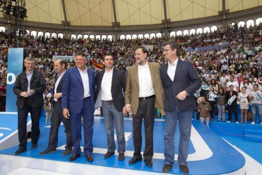 El presidente del PP, Mariano Rajoy (2d) posa junto al máximo responsable del partido en Galicia, Alberto Núñez Feijóo (3d); al candidato del PP a la alcaldía de Pontevedra, Telmo Martín (3i); el presidente de la Diputación de Pontevedra, Rafael Louzán (2i), y el conselleiro de Justicia, Alfonso Rueda (i), durante el acto de la precampaña para las próximas elecciones municipales que se ha celebrado esta tarde en la plaza de toros de Pontevedra.