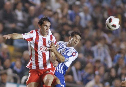 El centrocampista del Deportivo de La Coruña Juan Carlos Valerón (d) disputa un balón aéreo con el defensa uruguayo del Atlético de Madrid Diego Godín.