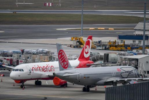 Un avión de la aerolínea Air Berlin detenido junto a otro de la aerolínea de bajo coste austríaca NIKI en la pista del aeropuerto internacional de Viena.