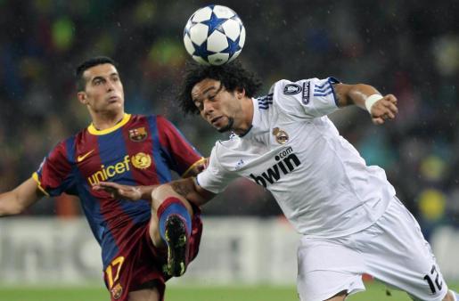 El defensa brasileño del Real Madrid Marcelo Vieira (d) pelea un balón con el delantero del F.C. Barcelona Pedro Rodríguez. Ambos jugadores marcaron los tantos del partido.