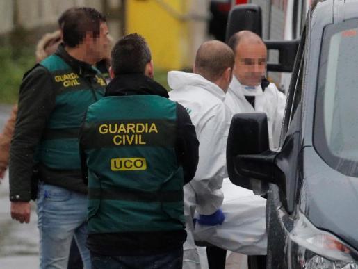 Efectivos de la Guardia Civil custodian la camilla los restos del cadáver encontrado en una nave industrial en la parroquia de Asados, en Rianxo (A Coruña).