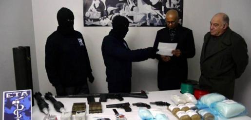 Dos encapuchados de ETA entregan el inventario de armas y explosivos a miembros del grupo de verificación.