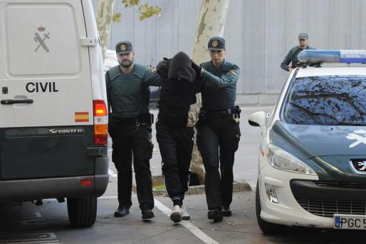 Dos agentes de la Guardia Civil acompañan ayer al homicida confeso a los calabozos del juzgado de guardia de Palma.
