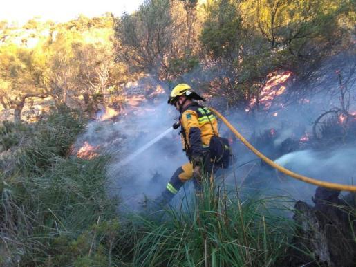Un bombero, apagando las llamas del incendio.