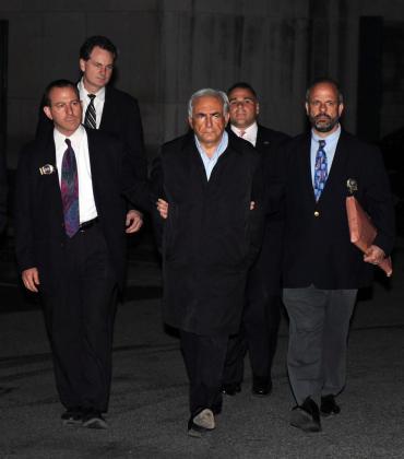 El director gerente del FMI, Dominique Strauss-Kahn (2d), a su salida ayer, domingo 15 de mayo de 2011, de una estación de la Policía de Nueva York tras ser detenido en el aeropuerto internacional John F. Kennedy a bordo de un avión que se disponía a despegar hacia París, por intento de violación a una camarera de un hotel de Nueva York.