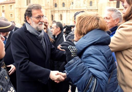 El presidente del Gobierno Mariano Rajoy (i), recibe el saludo de los vecinos, durante su visita institucional a León.