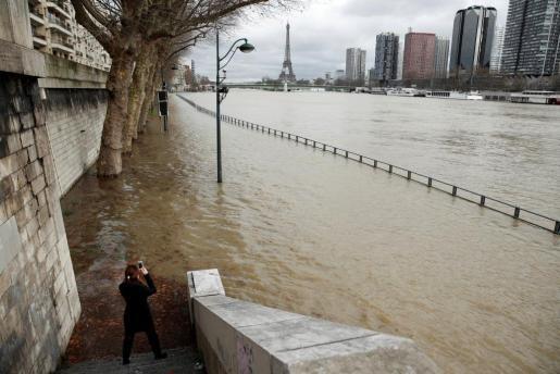 Una mujer fotografía la Torre Eiffel mientras el agua desborda el río Sena en París.
