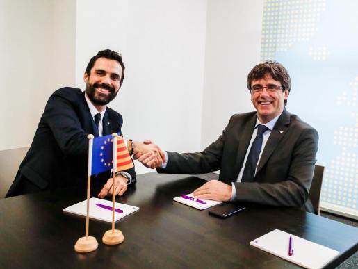 El expresidente de la Generalitat Carles Puigdemont estrecha la mano del presidente del Parlamento autónomo, Roger Torrent, durante su reunión en Bruselas.